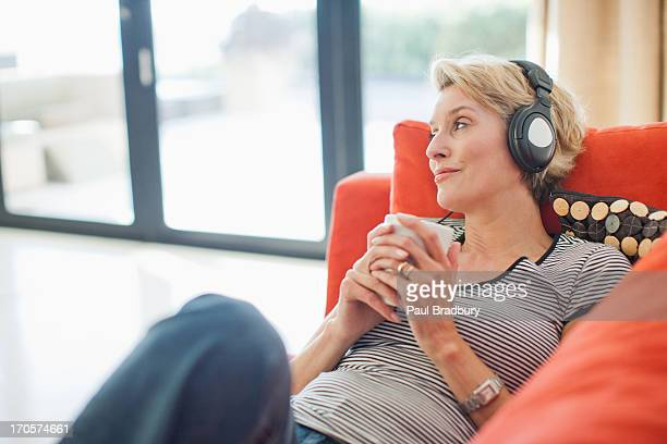 woman drinking coffee and listening to headphones - listening stock pictures, royalty-free photos & images