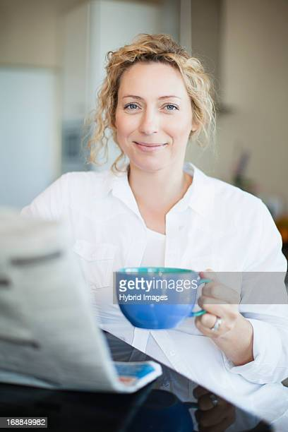 Woman drinking coffee and reading paper