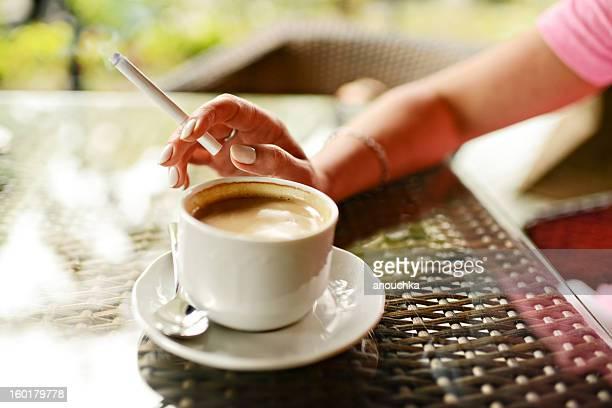 Woman コーヒーを飲みながら、喫煙は屋外カフェ