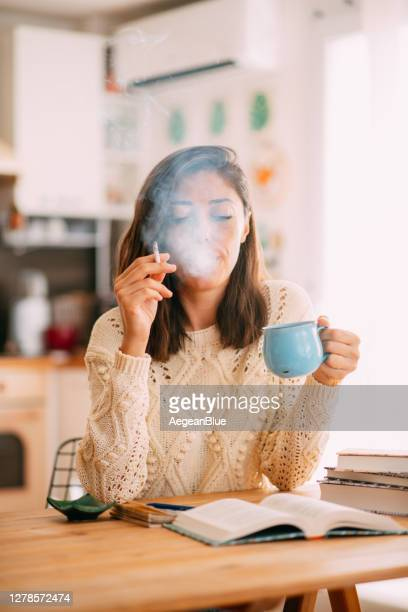 woman drinking coffee and smoking while reading book at home - caffeine stock pictures, royalty-free photos & images