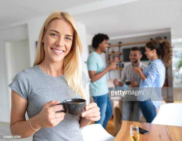 Woman drinking coffee at home with a group of flat mates