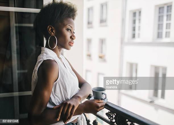 女性バルコニーでコーヒーを飲みながら、