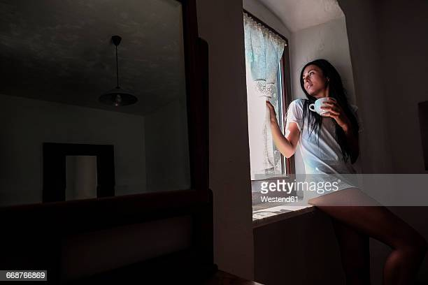 Woman drinking coffee, at window