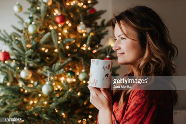 woman drinking coffee beside decorated christmas tree - serene people stock pictures, royalty-free photos & images