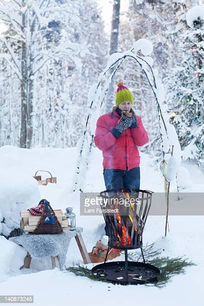 Femme buvant un café de Foyer dans la neige