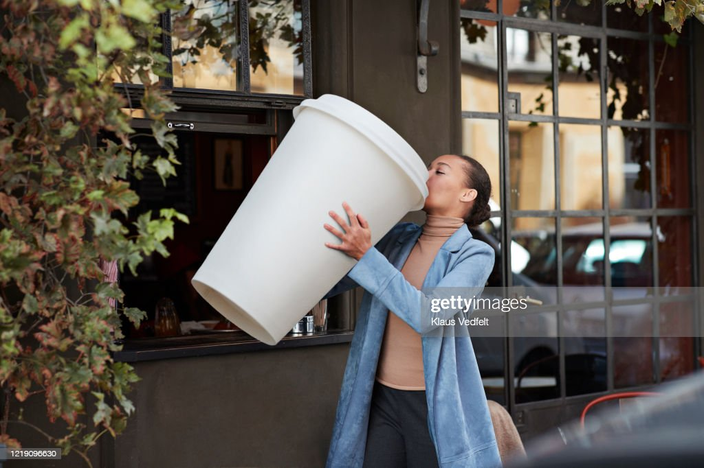 Woman drinking coffee from large disposable cup at take away counter of cafe : Stock Photo