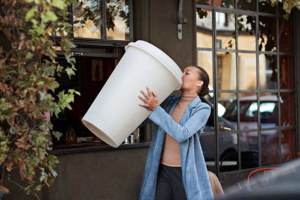woman drinking coffee from large disposable cup at take away counter of cafe - coffee cup sizes stock pictures, royalty-free photos & images