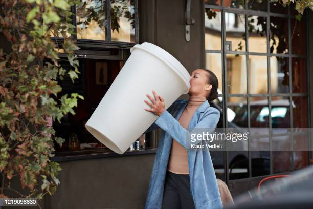 woman drinking coffee from large disposable cup at take away counter of cafe - コーヒー ストックフォトと画像