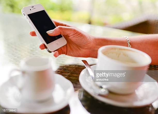 Woman drinking coffee holding iPhone in hands
