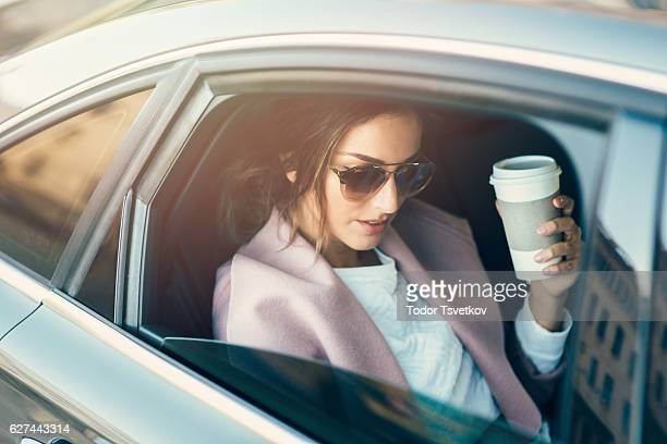 Woman drinking coffee in a car