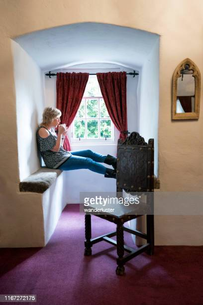 woman drinking coffee in a castle inn bedroom - needlecraft stock pictures, royalty-free photos & images