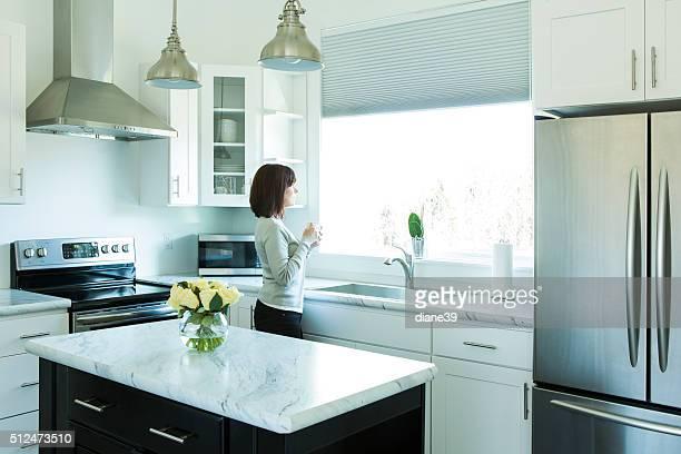 Mujer bebiendo café en una moderna cocina