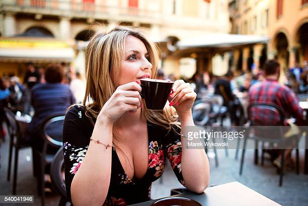 Woman drinking coffee in a sidewalk cafe in Bologna, Italy