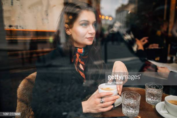 woman drinking coffee in cafe in paris, france - french cafe stock photos and pictures