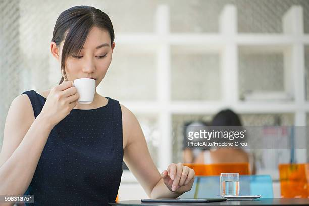 Woman drinking coffee in cafe, looking at digital tablet