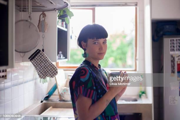 woman drinking coffee in her kitchen - showus stock-fotos und bilder