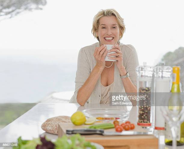 Woman drinking coffee in kitchen