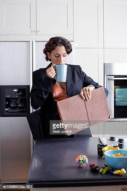 woman drinking coffee in kitchen - woman hurry stockfoto's en -beelden