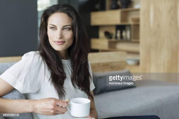 Woman drinking coffee in livingroom