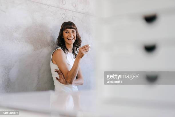 woman drinking coffee in office, leaning against wall - focus on background stock pictures, royalty-free photos & images