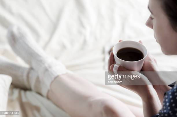 Woman drinking coffee in the bed