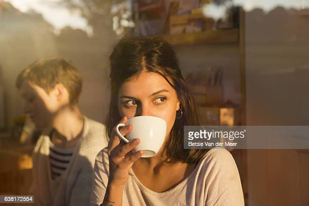 Woman drinking coffee in urban cafe while looking outside, sunny reflections in window.
