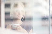 Woman drinking coffee indoors