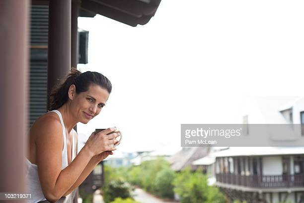 Woman drinking coffee on a cottage balcony