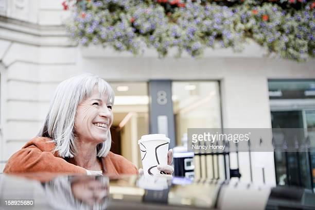 Woman drinking coffee on city street
