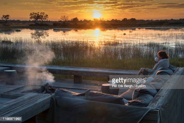 woman drinking coffee on sofa against lake during sunset - okavango delta stock pictures, royalty-free photos & images