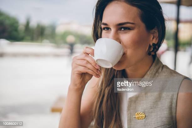 mujer bebiendo café al aire libre - brooch fotografías e imágenes de stock