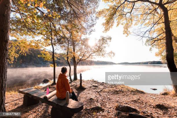 woman drinking coffee outdoors by the lake - sweden stock pictures, royalty-free photos & images
