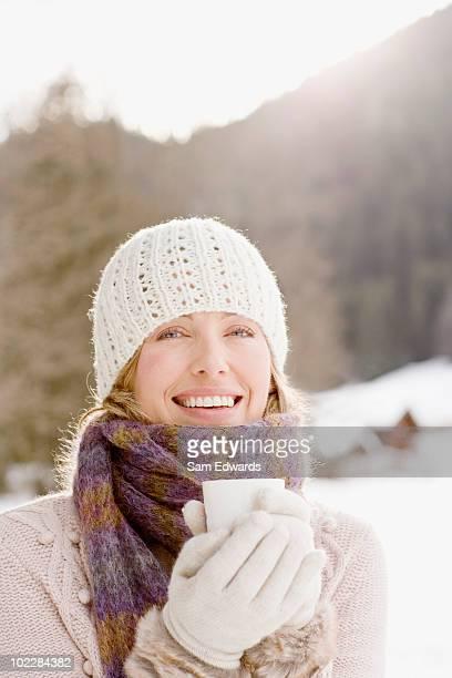 Frau trinkt Kaffee im Schnee