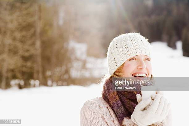 Woman drinking coffee outdoors in snow