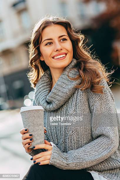 Woman drinking coffee outdoors