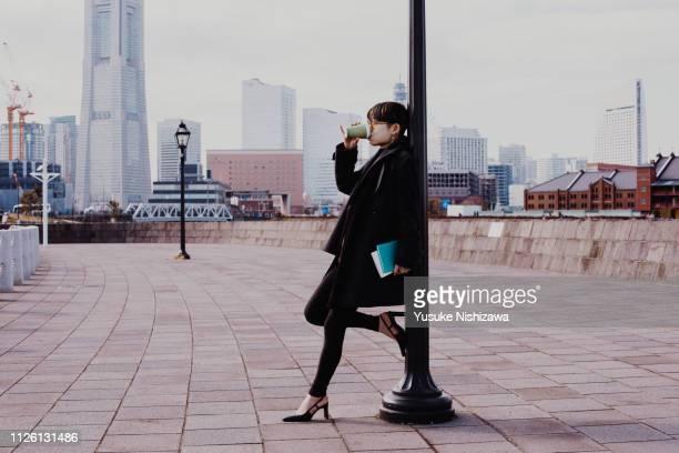 a woman drinking coffee - yusuke nishizawa ストックフォトと画像