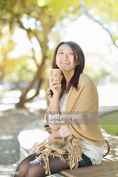 woman drinking coffee sitting on park bench - shawl stock pictures, royalty-free photos & images