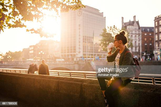 woman drinking coffee while sitting retailing wall of bridge in city - dublin stock pictures, royalty-free photos & images