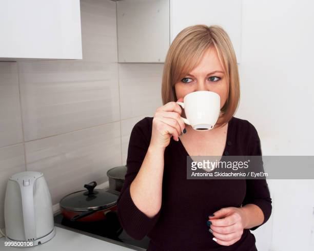 Woman Drinking Coffee While Standing At Kitchen