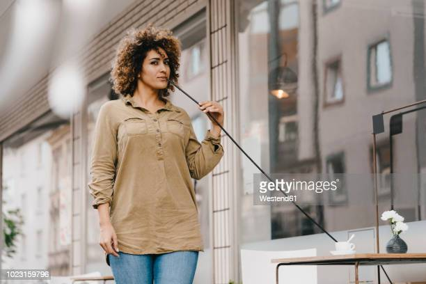 woman drinking coffee with oversized straw - extra long stock pictures, royalty-free photos & images