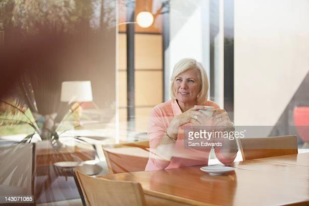 Mulher beber Xícara de café na mesa de cozinha