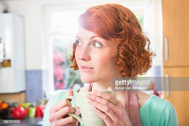 Woman drinking cup of tea in kitchen.
