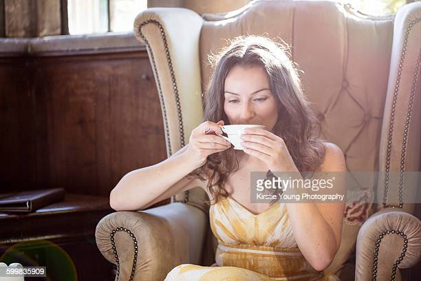 Woman drinking cup of tea in old armchair at Thornbury Castle, South Gloucestershire, UK