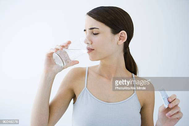 Woman drinking effervescent water, holding medicine packet