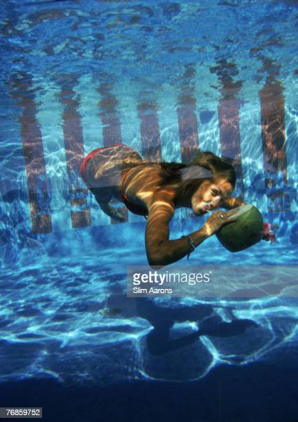 A woman drinking from a coconut underwater in the pool at Las Brisas Hotel in Acapulco Mexico February 1972
