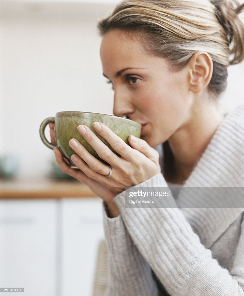 Woman Drinking From a Cup in a Kitchen : Stock Photo