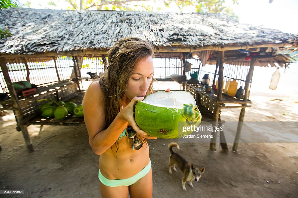 A woman drinking from a young fresh coconut. : Stock Photo