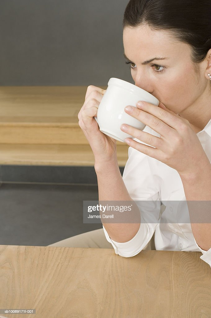 Woman drinking from cup : Stockfoto