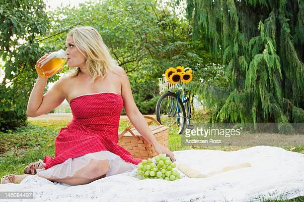 Mujer bebiendo del recipiente en un picnic