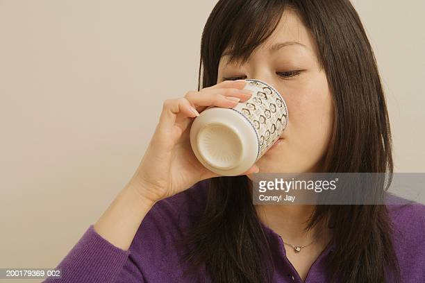 Woman drinking from mug, close-up